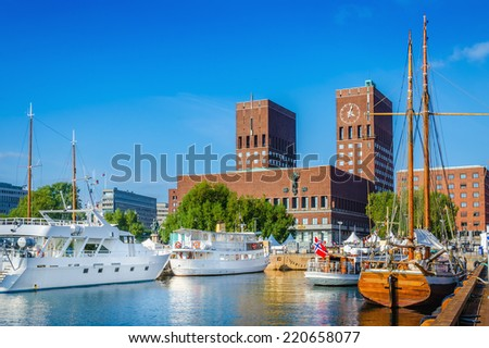 Harbor with boats and wooden yacht with town hall in Oslo, Norway - stock photo
