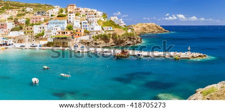 Harbour with marine vessels, boats and lighthouse. Panoramic view from a cliff on a Bay with beach Bali - vacation resort, with secluded beaches and clear ocean waters, Rethymno, Crete, Greece - stock photo