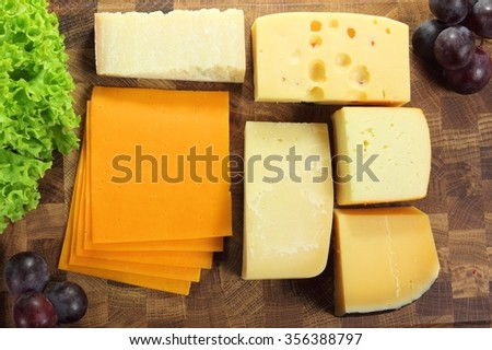 Hard cheeses served on a wooden board. - stock photo
