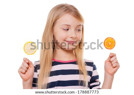 Hard choice. Cheerful little girl holding lollipops in her hands and smiling while standing isolated on white - stock photo