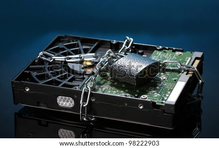 Hard disk drive on chain on dark blue background - stock photo