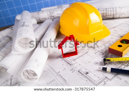 Hard hat with blueprints and rulers - stock photo