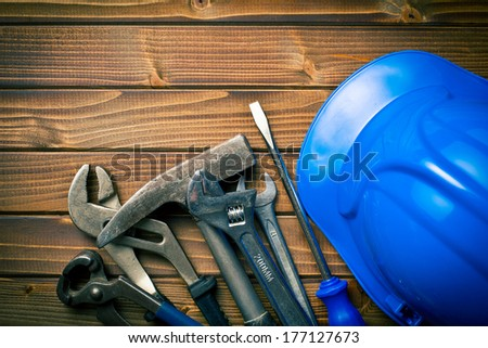 hard hat with various working tools on wooden background - stock photo
