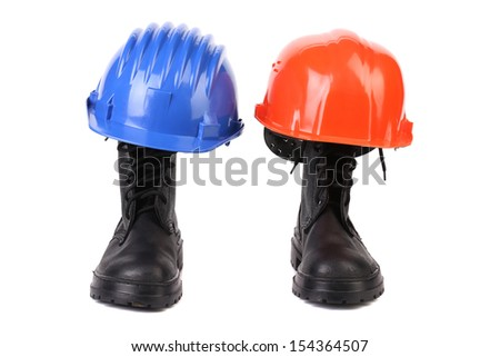 Hard hats and working boots. - stock photo
