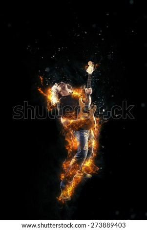 Hard rock heavy metal guitarist on fire playing his instrument - stock photo