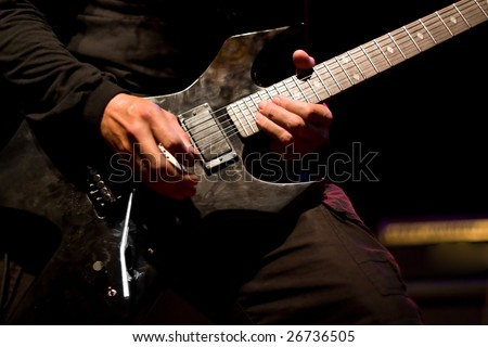 Hard Rock male Heavy Metal Guitarist playing black electric guitar in live music gig concert - stock photo