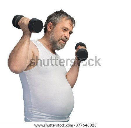 Hard work for a healthy lifestyle concept. Fat middle-aged man with a big belly does physical exercises with dumbbells isolated on white with copyspace - stock photo