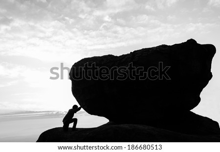 Hard work.The person rolls the rock on mountain. - stock photo