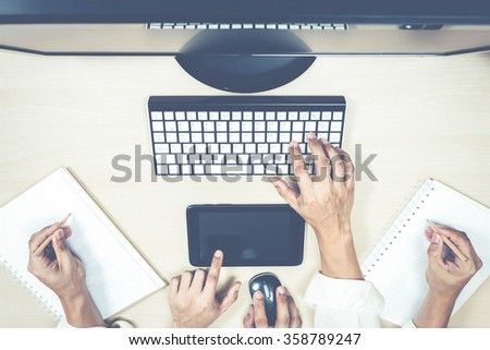 hard working asian businessman / male employee hands with computer on workspace desk in office + film filter - stock photo