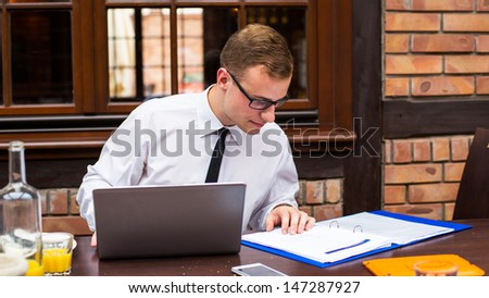 Hard working businessman in restaurant. Close-up. - stock photo