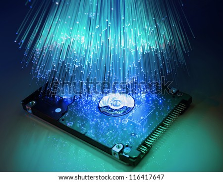 harddisk and heads on technology fiber optics background - stock photo