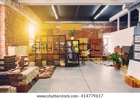 Hardware store office. Samples colored bricks. Brick wall interior. Sunlight from big window - stock photo