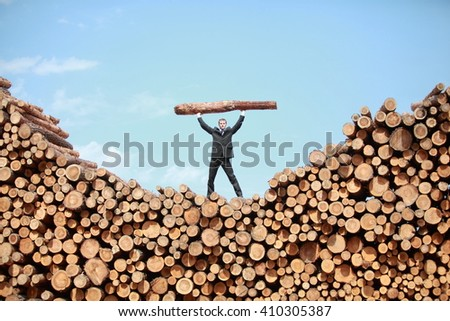Hardworking Business Man on top of large pile of logs   lifting  heavy log - front view - stock photo