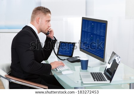 Hardworking businessman at his desk working on the computer screens simultaneously as he takes a call on his mobile phone - stock photo