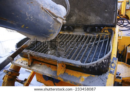Hardworking laborer and truck-concrete mixer on construction site - stock photo