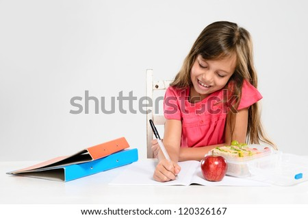 Hardworking studious cute school girl writes and does her homework with an apple and healthy packed lunch on the table - stock photo
