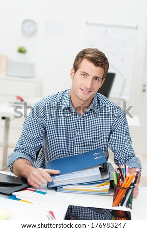 Hardworking successful handsome young businessman sitting at a desk littered with files, paperwork and a desktop computer smiling at the camera - stock photo
