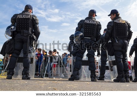 HARMICA, CROATIA: SEPTEMBER 20, 2015: Policemen behind the barrier dividing group of immigrants and refugees from Middle East and North Africa at Harmica, state border between Slovenia and Croatia. - stock photo