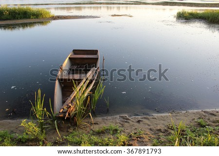 harmonious landscape for meditation: dawn at the Don river, Russia. The first rays of the sun warm light smooth water and the old fishing boat - stock photo