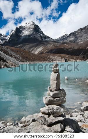 Harmony: Stone stack and Sacred Lake near Gokyo. Travel to Nepal - stock photo