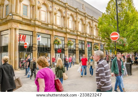 Harrogate, UK - September 27, 2014: Locals and Tourists strolling around the city centre lined with shops. Harrogate is consistently voted as one of the best places to live in the UK.  - stock photo