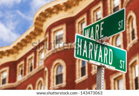 Harvard street sign with a classic red brick building in the background . Location: Harvard University in Cambridge, Massachusetts, USA. - stock photo