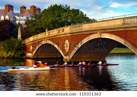 Harvard University crew team in a scull going under the Weeks Bridge on the Charles River.  Beautiful golden morning light and reflections on the water. - stock photo