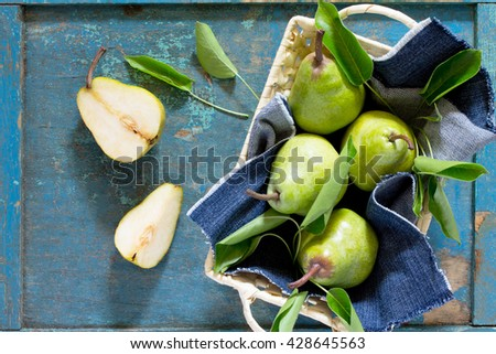 Harvest fresh organic juicy pears in a wicker basket on a rustic wooden table, top view with copy space. - stock photo