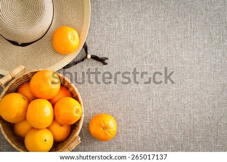 Harvest of farm fresh succulent ripe oranges with a straw sunhat direct from the farmer on a beige cloth background with copy space viewed from overhead in a healthy diet and nutrition concept - stock photo