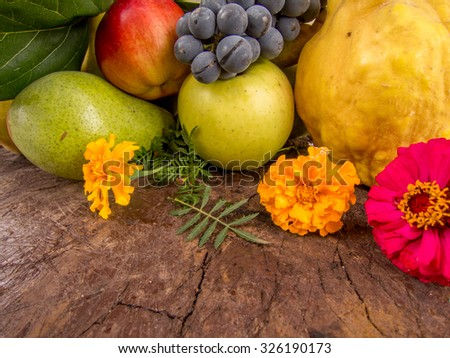 harvest of grapes quinces pears and apples with autumn flowers - stock photo