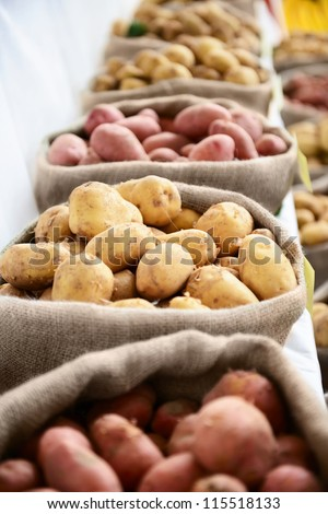 Harvest raw potatoes in burlap sack in market - stock photo