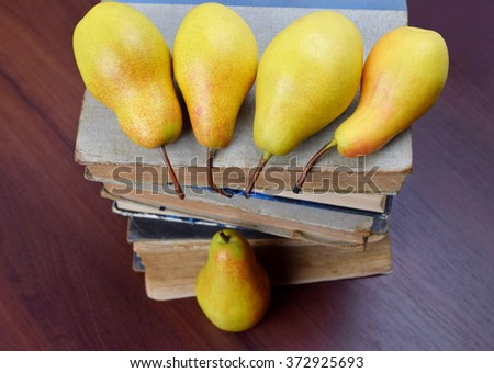 Harvest ripe fragrant pears on old books. Concept: the result of the study of books on gardening, the first harvest.((The concept:  loneliness outside of society) can be?) - stock photo