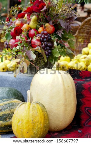 Harvested pumpkins with fall flowers on the background - stock photo