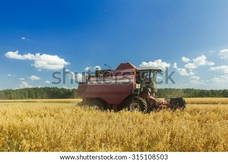 Harvesting combine machine with reel and the cutter bar is harvesting oats on farm field  - stock photo