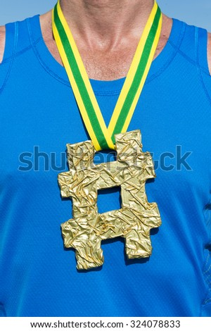 Hashtag gold medal athlete in blue shirt outdoors close-up - stock photo