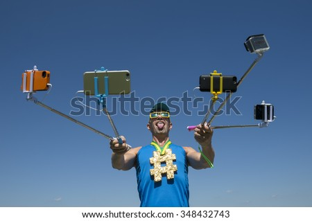 Hashtag gold medal athlete posing with his tongue out for his many gadgets on selfie sticks  - stock photo