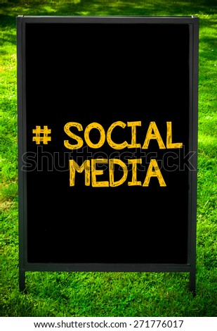 Hashtag Social Media message on sidewalk blackboard sign against green grass background. Copy Space available. Concept image - stock photo