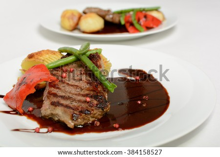 Hasselback potatoes with beef and red wine sauce  - stock photo