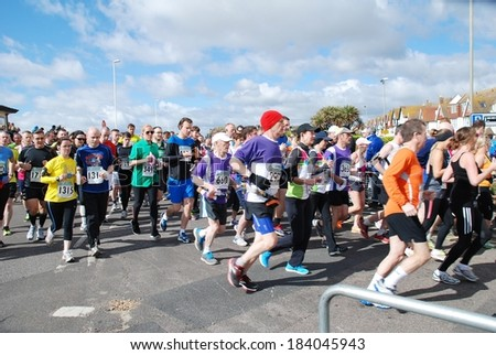 HASTINGS, ENGLAND - MARCH 23, 2014: Runners take part in the annual Hastings Half Marathon race at Hastings in East Sussex. This was the 30th year the event has been held. - stock photo