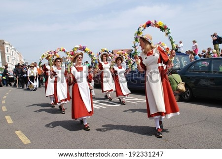 HASTINGS, ENGLAND - MAY 5, 2014: Members of the Copperfield Clogs morris dancing team perform during a parade on the West Hill at the annual May Day Jack In The Green festival.  - stock photo