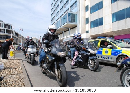 HASTINGS, ENGLAND - MAY 5, 2014: Motorcyclists ride along the seafront during the annual May Day biker rally. Started over 35 years ago, the event is now one of the largest bike gatherings in Britain. - stock photo