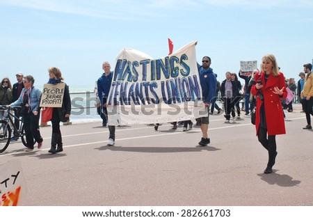 HASTINGS, ENGLAND - MAY 30, 2015: Protestors take part in a march along the seafront to demonstrate against austerity measures and Government cutbacks after the Conservatives won the General Election. - stock photo