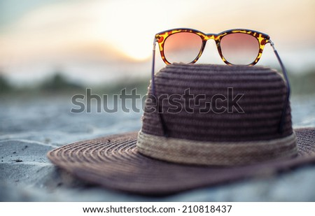 Hat and glasses lie on a beach at a beautiful sunset - stock photo