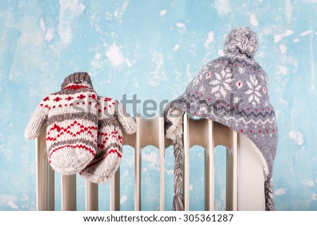 hat and gloves on a radiator / heater on a blue cold winter background - stock photo