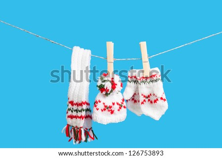 hat, scarf and pair of gloves drying in the open air hanging on clothes line affixed with wooden pegs - stock photo