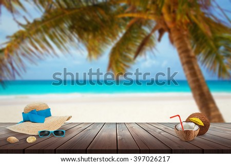 Hat, sunglasses, coconut, shell on beach table. Free space for text. Beach, sea, palm and blue sky in background. - stock photo