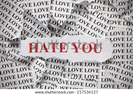 "Hate you. Torn pieces of paper with the word ""Love"" and phrase ""Hate you"" in red color. Closeup.  - stock photo"