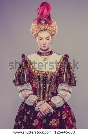 Haughty queen in royal dress isolated on grey - stock photo