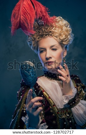 Haughty queen in royal dress with mirror - stock photo