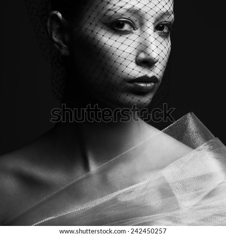 Haute couture concept. Portrait of mysterious beautiful brunette looking at camera through black veil and posing over black background. Silver eyebrows, wet lips. Close up. Vogue style. Studio shot - stock photo